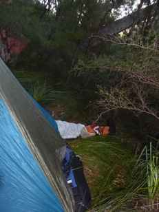 Mike half in the tent after a night camped on a slope.